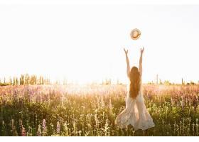 日落时分年轻女子在花田里扔草帽_333917401