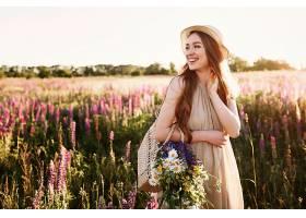 日落时分快乐的小女孩走在花田里戴着草_333916101