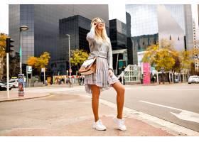 时尚女性的全长户外形象用智能手机说话_985550301
