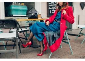 时尚女性的时尚配饰穿着红色外套坐在城市_1068763501