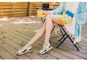 特写年轻女子穿着夏装坐在躺椅上的细节_940550001