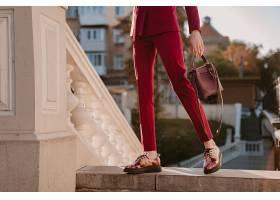 特写时尚女性穿着紫色西装走在城市街道上_1155516401