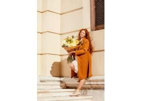时髦的女人在户外开着一束春天的鲜花_1239682401