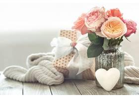 用玻璃花瓶里的一束玫瑰花和礼盒组成的构图_1192484901