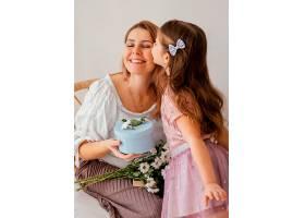 小女孩在母亲节送给妈妈春天的鲜花和礼盒_1222474201