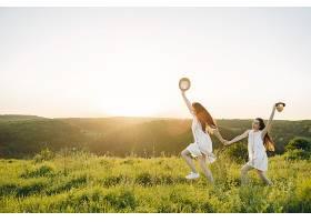 田野里两个穿着白色连衣裙留着长发的姐妹_965887601