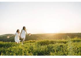 田野里两个穿着白色连衣裙留着长发的姐妹_965887801