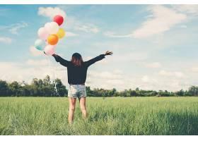 田野里拿着气球的女孩_90799701