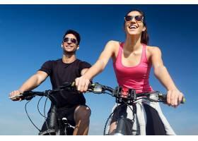 幸福的年轻夫妇在乡下骑自行车_123238301