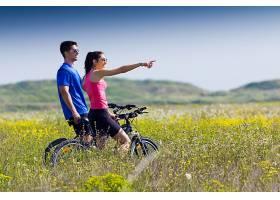 幸福的年轻夫妇在乡下骑自行车_123239101