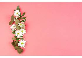 桃色背景上由白色雏菊花叶制成的装饰品_390263001