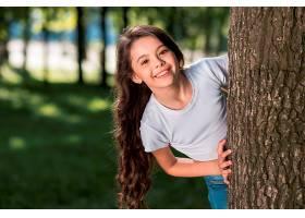 微笑的可爱女孩在户外从树干后面向外看_500049301