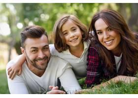微笑的夫妇带着他们的女儿躺在草坪上_98703301