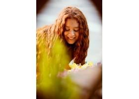 微笑的女人在户外得到春天的鲜花_1239684901