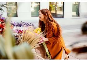 微笑的女人在户外得到春天的鲜花的侧观_1239685201