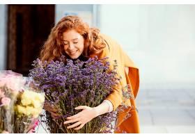 微笑的女人带着一束春天的鲜花在户外免费拍_1239682001
