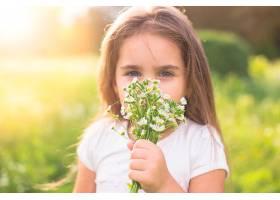 一个女孩闻到白色花香的特写_307535001