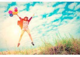 一个拿着彩色气球在海滩上跳跃的女孩_90796801