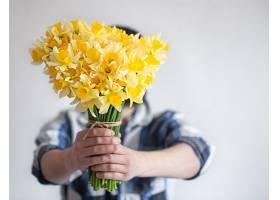 一个穿衬衫的男人用一束鲜花遮住了他的脸_1156713301