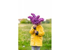 一个穿黄色夹克的小女孩用一束紫丁香遮住了_1156717201