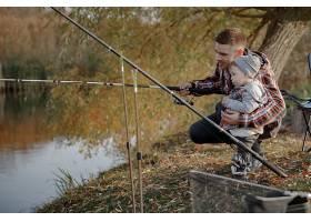 一个钓鱼的早晨父亲带着年幼的儿子在河边_716966101