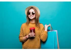 一位年轻女子拿着咖啡带走拿着购物袋在_907681001