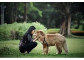 一位年轻漂亮的女士在户外公园里和她的小狗_547399501