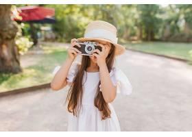 一位留着黑色长发的小女孩手里拿着相机_1048514401