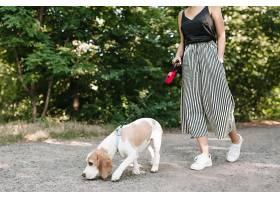 一位穿着复古条纹裤子的女子走在公园里而_1056246301