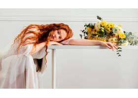一位美女在桌上摆着一束春花的姿势_1239684201
