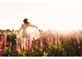 一位身着婚纱的美丽新娘正独自在麦田里跳舞_333916801