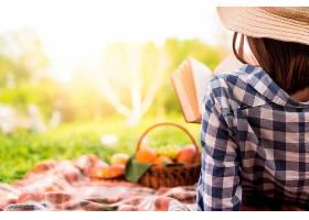一名女子在公园里放松地看书_472477101