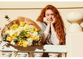 一名女子手持一束春花在户外摆姿势_1239682701