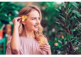 一名年轻女子将黄花放在耳朵后面的特写_391156201
