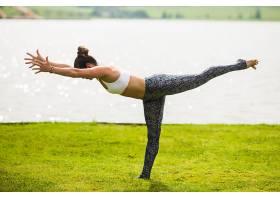 一名年轻女子早上在阳光照射下在公园摆瑜伽_1209804501