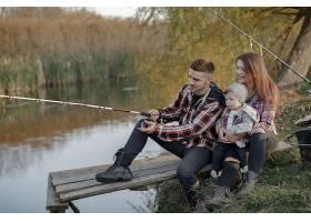 一家人在钓鱼的早晨坐在河边_716968201