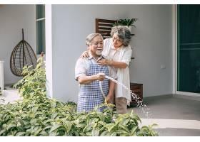 一对老年夫妇在自家花园里浇花_410796501