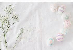 一排复活节彩蛋图案靠近植物枝条和纺织品_400232901