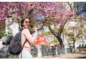 兴奋的女人背着背包指着盛开的树_453014001