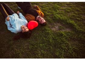 年轻夫妇手持红心气球躺在草地上_362464101