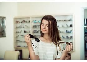 年轻女子在购物手里拿着两副时髦的太阳镜_770589901