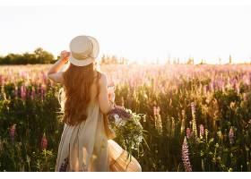年轻女子戴着草帽穿着一束羽扇豆花_333916501