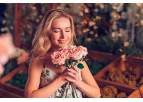 年轻女子闻到粉色玫瑰的特写_388266401