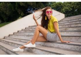 年轻漂亮时髦的微笑女子在城市公园里玩耍_1088494801
