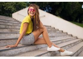 年轻漂亮时髦的微笑着的女人在城市公园里玩_1088494501