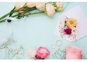 蓝色粉色背景上的结婚戒指和鲜花装饰_345349601