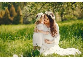 年轻漂亮的怀孕女孩穿着白色长裙和小女孩玩_253453401