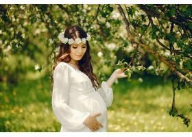 年轻漂亮的怀孕女孩穿着白色长裙头上戴_253453801