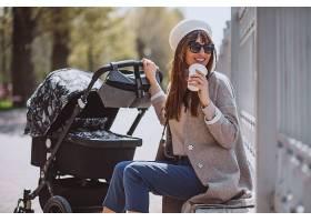 年轻的母亲推着婴儿车在公园里散步_475859001