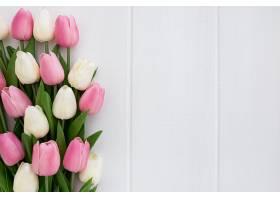 白色木质背景上的一束可爱的郁金香右边有_382656201